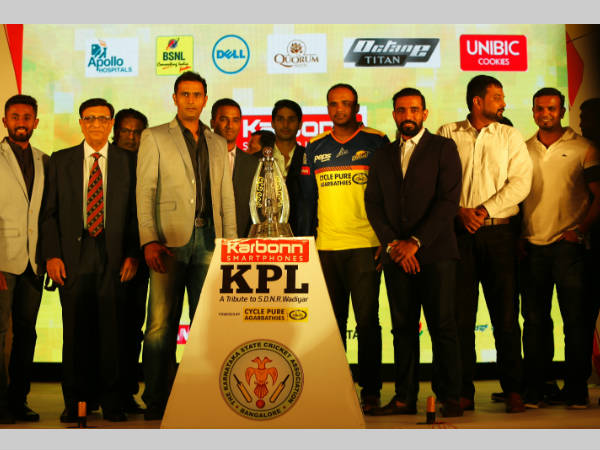The players and officials pose in front of KPL trophy