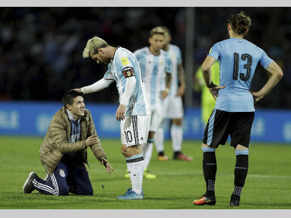 A fan who invaded the pitch kneels in front of Argentina's Lionel Messi, centre, as Uruguay's Gaston Silva looks on during a 2018 World Cup qualifying match in Mendoza, Argentina, on Thursday (September 1).