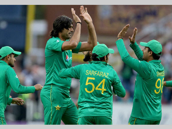 Pakistan's Mohammad Irfan (2nd left) and his team-mates celebrate a wicket against England