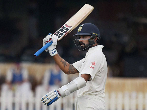 Indian batsman Murali Vijay raises his bat after completing a half-century on the opening day of the first Test match against New Zealand at Green Park