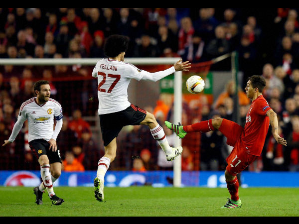 Liverpool's Roberto Firmino, right, goes for the ball with United's Marouane Fellaini during the Europa League round of 16, first leg, soccer match between Liverpool and Manchester United at Anfield Stadium, Liverpool, England, on March 10, 2016.