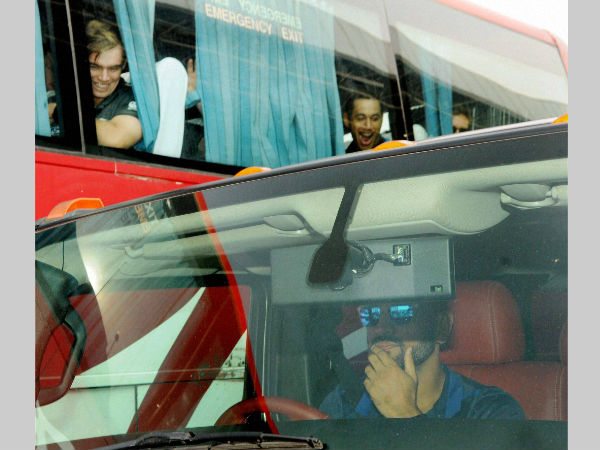 Dhoni (right) drives his Hummer as New Zealand cricketers (left) in a bus, are stunned, in Ranchi on Tuesday (October 25)