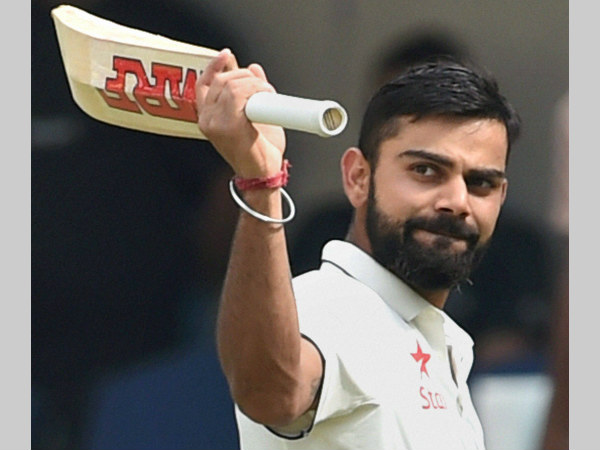Virat Kohli waves to the crowd as he heads back to the pavilion after being dismissed for 211 against New Zealand in Indore Test