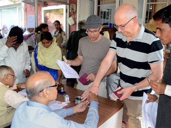 Tourists get indelible ink applied