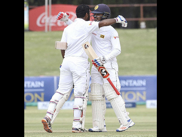 Sri Lanka batsman Dimuth Karunaratne, right, and Dhananjaya de silva hug during the test cricket match against Zimbabwe at Harare Sports Club in Harare, Tuesday