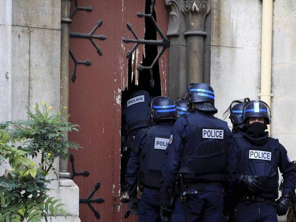 French police officers storm a church