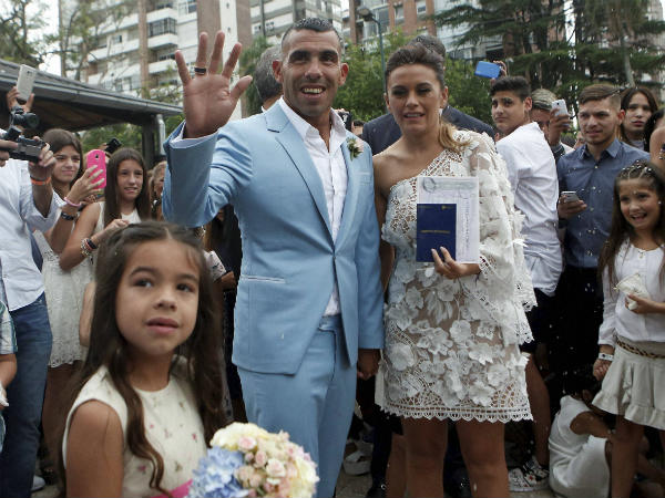 Carlos Tevez and his wife Vanesa Mansilla pose for photos after exiting the church where they married in in Buenos Aires, Argentina, Thursday, December 22