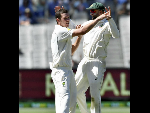 Australia's Josh Hazlewood, left, celebrates with team mate Nathan Lyon, right, capturing the wicket of Pakistan's Azhar Ali on the fifth day of their second cricket test in Melbourne