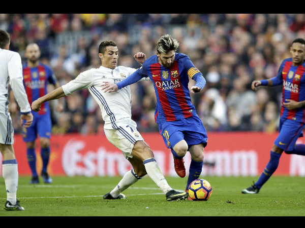 Barcelona's Lionel Messi, center right, escapes Real Madrid's Cristiano Ronaldo during the Spanish La Liga soccer match between FC Barcelona and Real Madrid at the Camp Nou in Barcelona, Spain