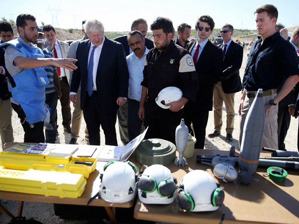 British Foreign Secretary Boris Johnson, third left, speaks with Syrians who are being educated by British bomb disposal experts during his visit to the Syrian refugee camp in Nizip in Gaziantep province, Turkey, Monday, Sept. 26, 2016.