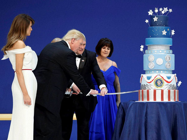 First lady Melania Trump watches as President Donald J. Trump, and Vice President Mike Pence cut a cake at The Salute To Our Armed Services Inaugural Ball in Washington. Karen Pence watches at right.