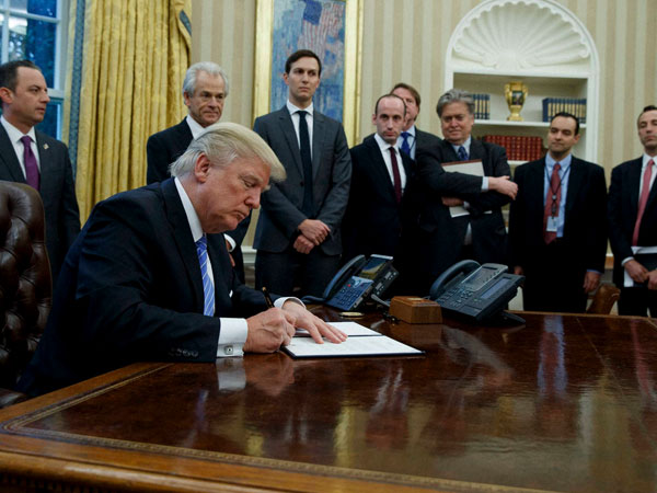 President Donald Trump signs an executive order in the Oval Office of the White House in Washington.