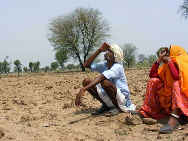 Farmer sitting on dry land.