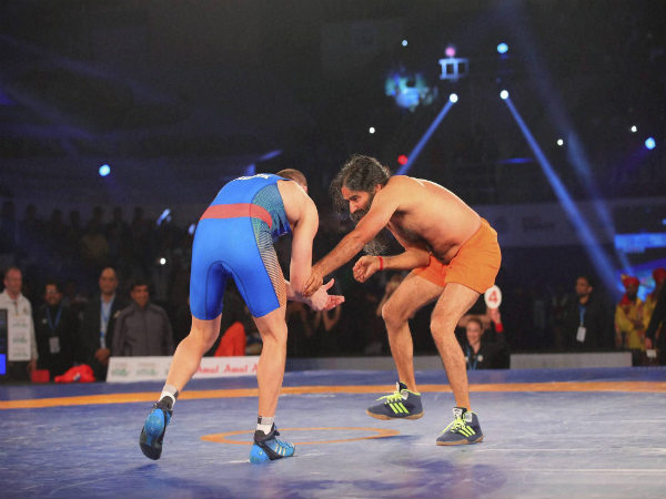 Baba Ramdev (right) fight against Olympic medalist Andrey Stadnik during friendly wrestling bout in PWL