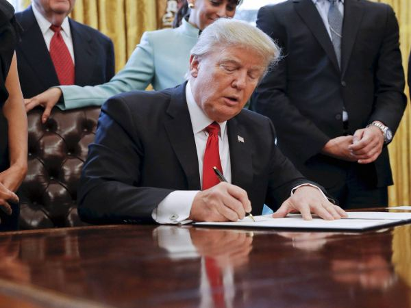 President Donald Trump, surround by small business leaders, signs an executive order in the Oval Office of the White House in Washington.