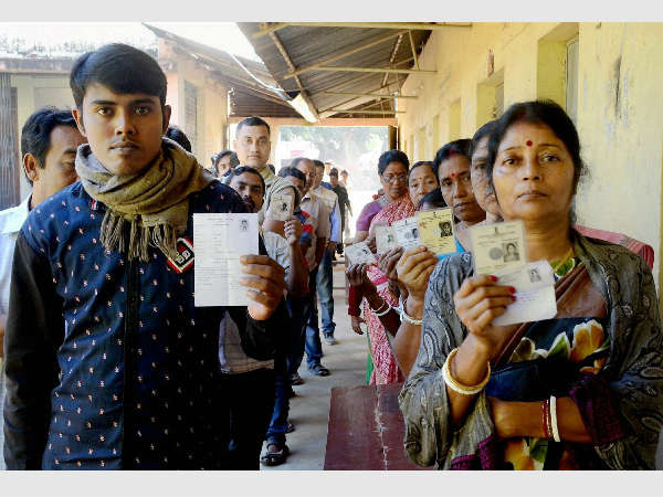 Voters show their voter identity cards as they wait in queues to cast their vote.