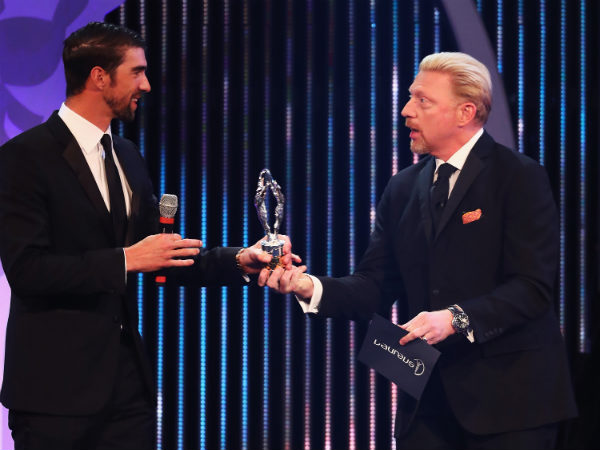 Michael Phelps (left) collects his award from Boris Becker