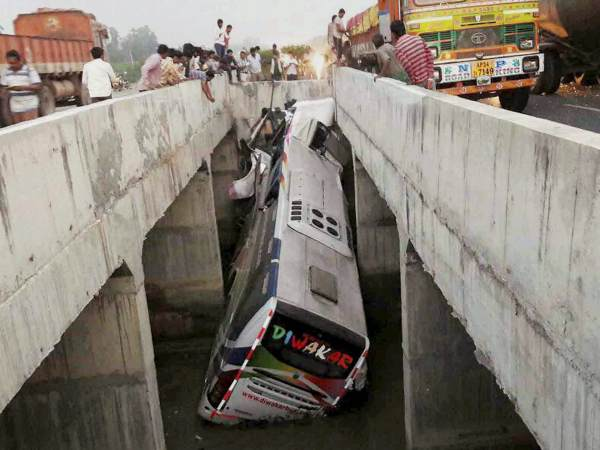 People looking at a private bus after it fell off a bridge into a canal in Vijayawada