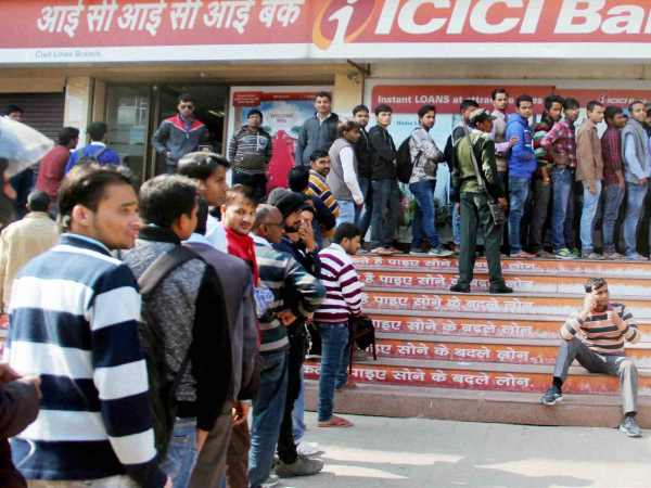 People stand in long queues outside an ATM at a bank to withdraw cash after the ban on old high denomination notes.