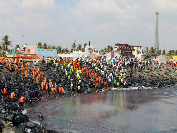 Firefighters and volunteers try to clean up oil that has washed ashore in Chennai.