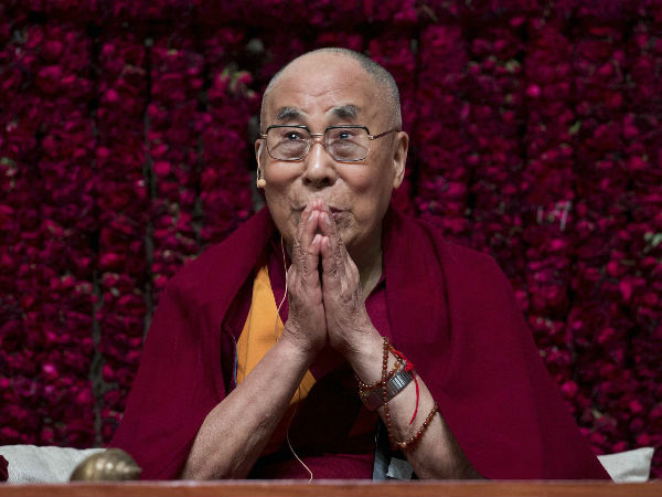 Tibetan spiritual leader the Dalai Lama gestures as he speaks.
