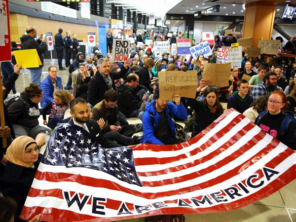 "Demonstrators sit down in the concourse and hold a sign that reads ""We are America,"" as more than 1,000 people gather at Seattle-Tacoma International Airport, to protest President Donald Trump's order that restricts immigration to the U.S."