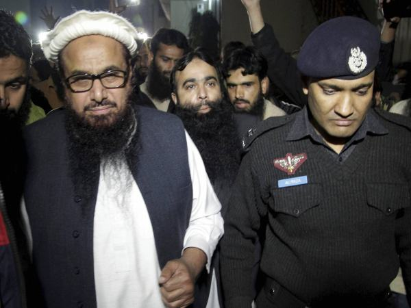 A Pakistani police officer escorts Hafiz Saeed in Lahore, Pakistan.