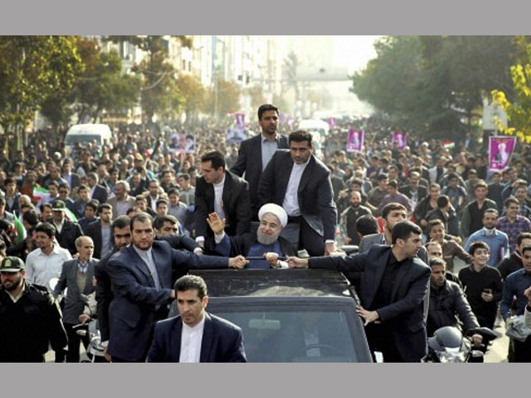 In this photo released by an official website of the office of the Iranian Presidency, Iranian President Hassan Rouhani, center, waves to his well-wishers from his car during a public welcoming ceremony for him upon his arrival.