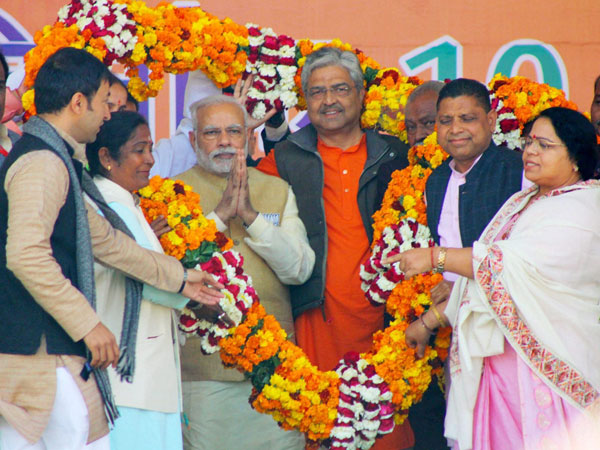 Prime Minister Narendra Modi is garlanded at a BJP election rally in Bijnor.