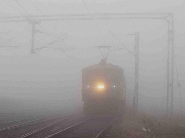 A train moves slowly amid a thick blanket of fog on a cold morning, in Allahabad.