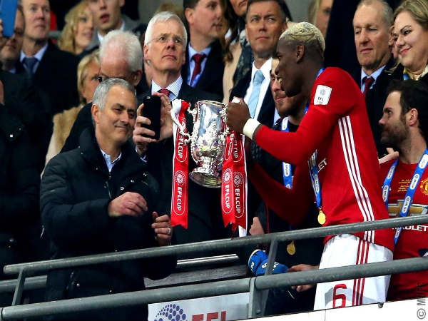 Jose Mourinho (left) taking the EFL trophy from Paul Pogba (Image courtesy: Manchester United Twitter handle)