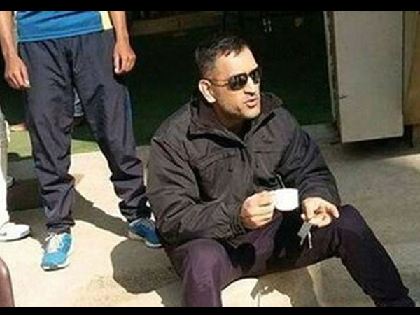Dhoni sipping tea while sitting on the ground