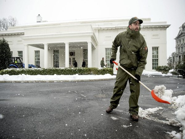 Workers clear snow outside the West Wing of the White House