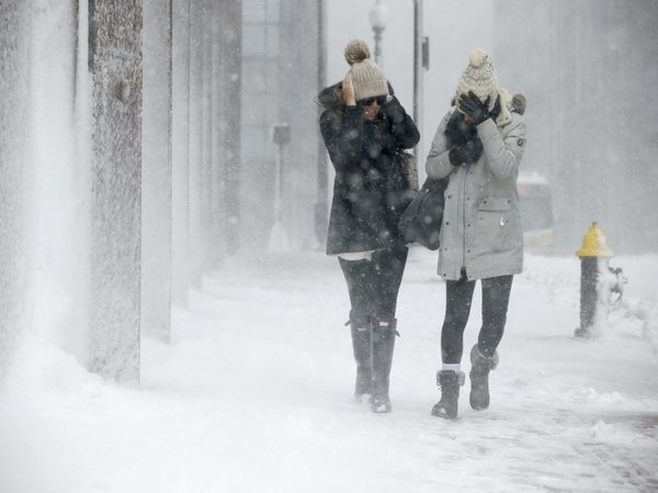 Two women struggle to walk in the blowing snow in Boston