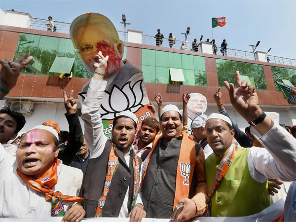 BJP supporters celebrate as early trends show the party's win in the Uttar Pradesh and Uttarakhand assembly polls, at the party office in Lucknow.
