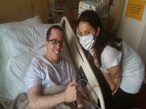 David Levy, the first adult patient cured of rare blood disorder cheers with his sister.