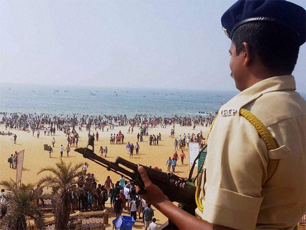 Policeman keep vigil on the shoreline as tourists enjoy at Calangute beach in Goa.