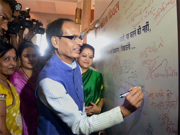 Madhya Pradesh Chief Minister Shivraj Singh Chouhan signing a board to extend his wishes during an exhibition organised on International Women's Day in the state assembly in Bhopal.