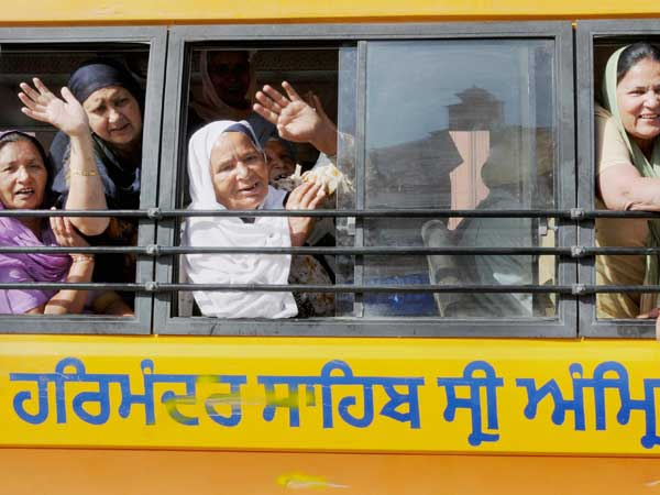 Sikh wave from a bus as they leave to board a special Pakistan-bound pilgrimage train to celebrate Baisakhi