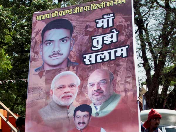 Workers carry a hoarding outside Delhi BJP office