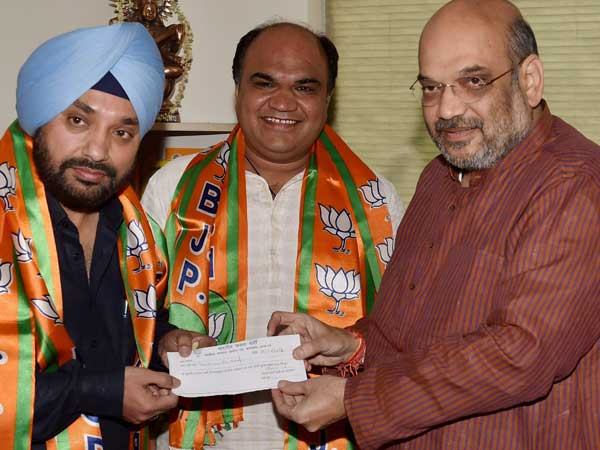 BJP President Amit Shah presents the party membership slip to former DPCC President Arvinder Singh Lovely as he joins BJP.