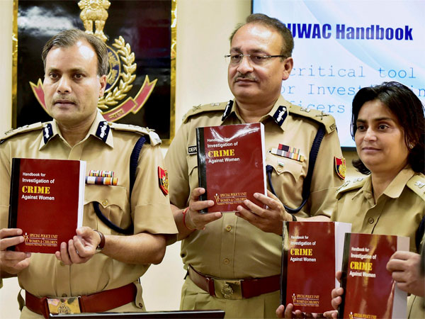 "Amulya Patnaik, Delhi Police commissioner, (L) with officials releases a book after launching improved ""HIMMAT"" app with new features on women's safety."