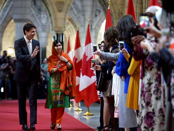 Pakistani activist and Nobel Peace Prize winner Malala Yousafzai, right, walks through the hall of honour with Prime Minister Justin Trudeau on Parliament Hill in Ottawa.
