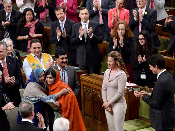 Pakistani activist and Nobel Peace Prize winner Malala Yousafzai, center, is hugged by her mother, Tor Pekai Yousafzai, as she's paid tribute in the House of Commons.