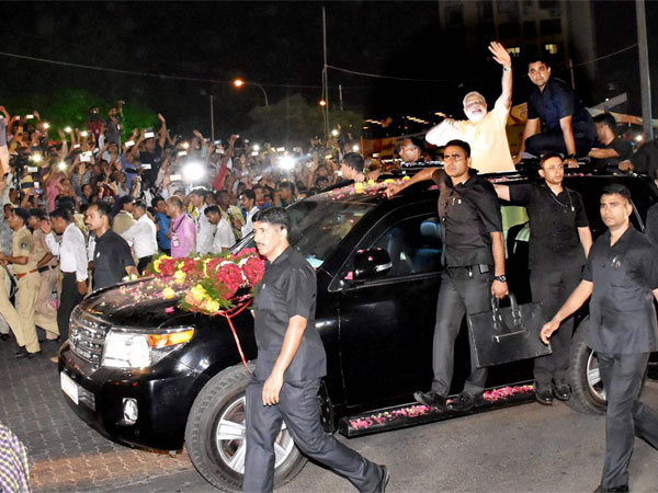 Prime Minister Narendra Modi waves at people during a road show in Surat.