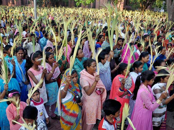 Christian devotees wave palm branches during special mass on 'Palm Sunday'. Photo credit: PTI