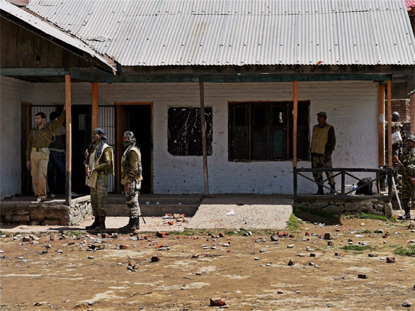 CRPF personnel standing guard at a polling station during repoll in Srinagar Lok Sabha constituency in Budgam district of Kashmir