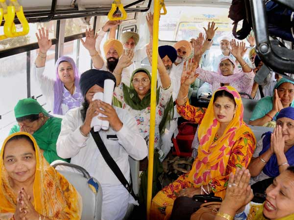 Sikh devotees shout religious slogans as they leave to board a special pilgrimage train bound for Pakistan