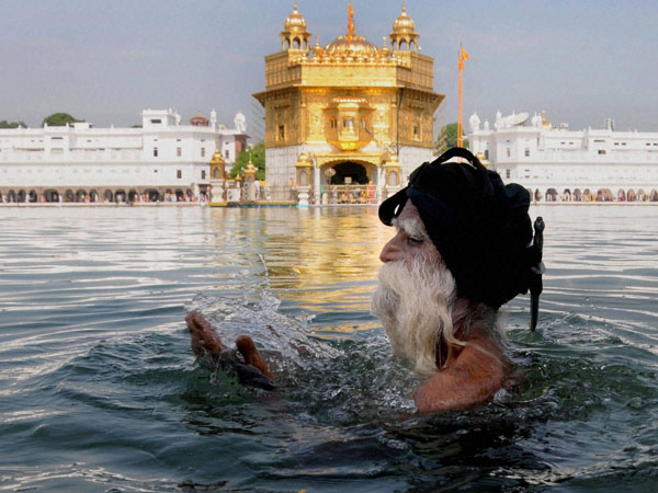 A Sikh devotee takes holy dip in the sacred pond of the Golden Temple on the occasion of the 412th anniversary of Sri Guru Granth Sahib in Amritsar. PTI file photo