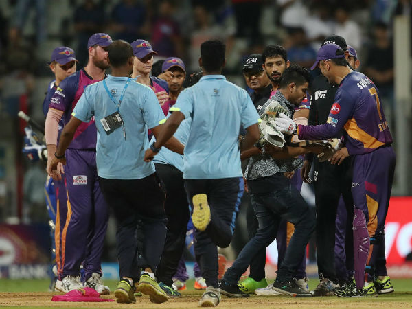 A pitch invader reaches to take autograph from MS Dhoni on the field during The Qualifier 1 match.